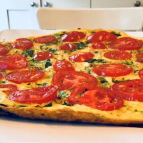 A large, round frittata on a white plate.