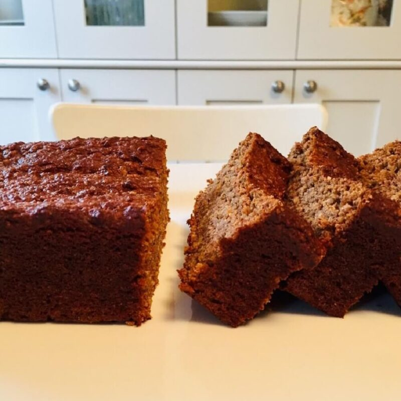 A big slab of banana bread next to some more slices on a platter.