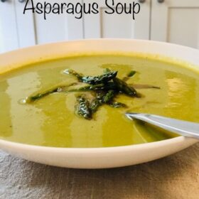 A bowl of asparagus soup with a spoon.