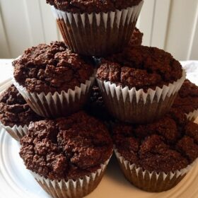 A stack of chocolate muffins on a plate.