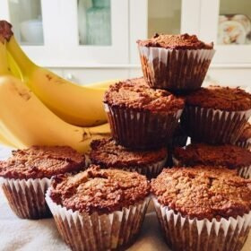 A bunch of bananas next to a stack of muffins.