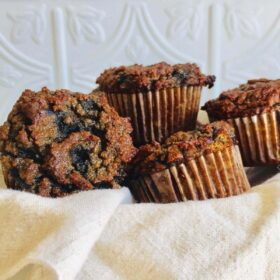 A basket filled with paleo blueberry banana muffins against a white tile background.