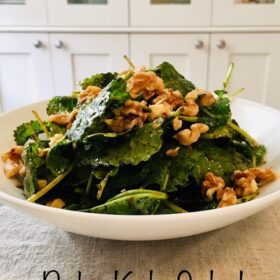 A big bowl of salad with walnuts sprinkled on top.