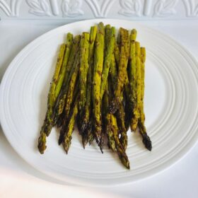 A white plate full of balsamic roasted asparagus against an intricate tile back splash.