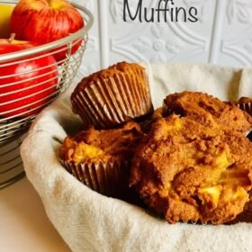 A basket of muffins next to some apples.