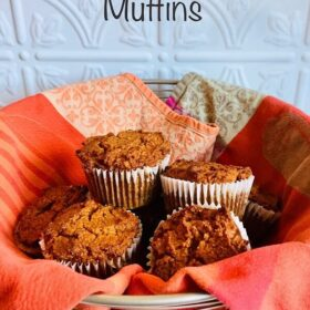 A basket of muffins with an orange and red cloth.