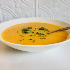 A white bowl of butternut squash soup with chives sprinkled on top.