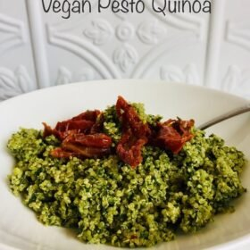 A bowl of green quinoa with red sun dried tomatoes on top and a spoon.
