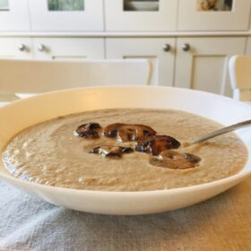 Dairy free cream of mushroom soup in a white bowl with a spoon.