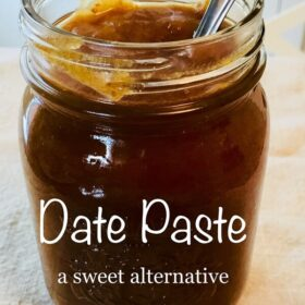 date paste in a jar with a metal spoon.