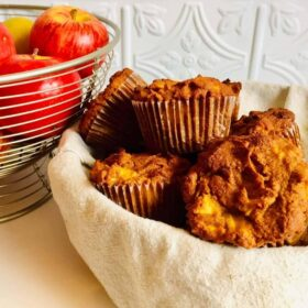 Muffins in a basket next to a wire bowl filled with apples