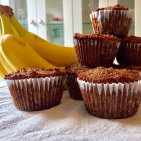 Some grain free banana muffins stacked next to a bunch of bananas.