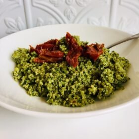 Pesto quinoa in a white bowl with a few sun dried tomatoes on top.
