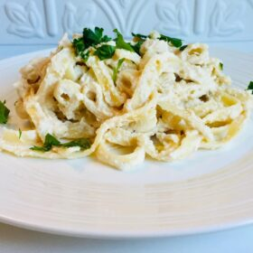 A plate filled with pasta smothered in cashew alfredo sauce with green parsley leaves sprinkled on top.