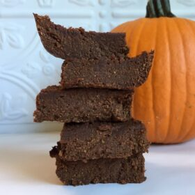 Five vegan pumpkin brownies piled next to a pumpkin against a white tile background.