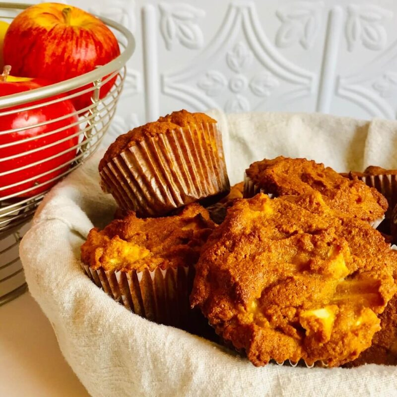 Muffins in a basket next to some apples.