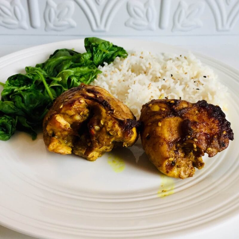 A white plate of chicken thighs, spinach, and rice against a white background.
