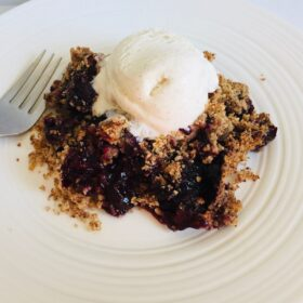 A serving of gluten free berry crisp on a plate with vanilla ice cream melting on top next to a fork.