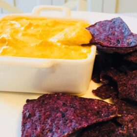 A white dish of dairy free cheese sauce next to a pile of blue corn chips.