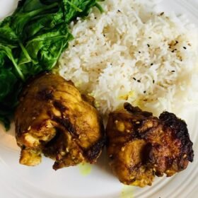 A plate of generous portions of chicken, rice, and spinach.