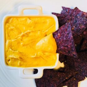 A dish of bright yellow vegan cheese sauce next to some corn chips