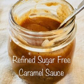 A glass jar of caramel with a spoon.