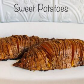 Hasselback sweet potatoes on a white plate.