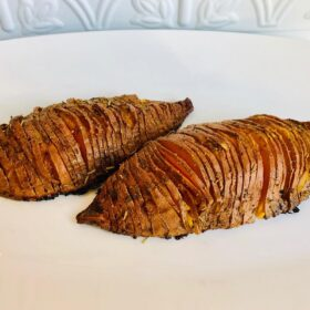 A white platter with two vegan hasselback sweet potatoes with slits cut in them..
