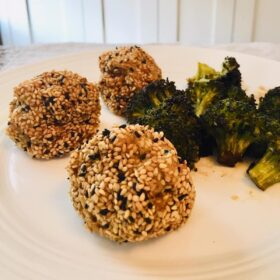 Paleo chicken meatballs on a white plate with some broccoli.