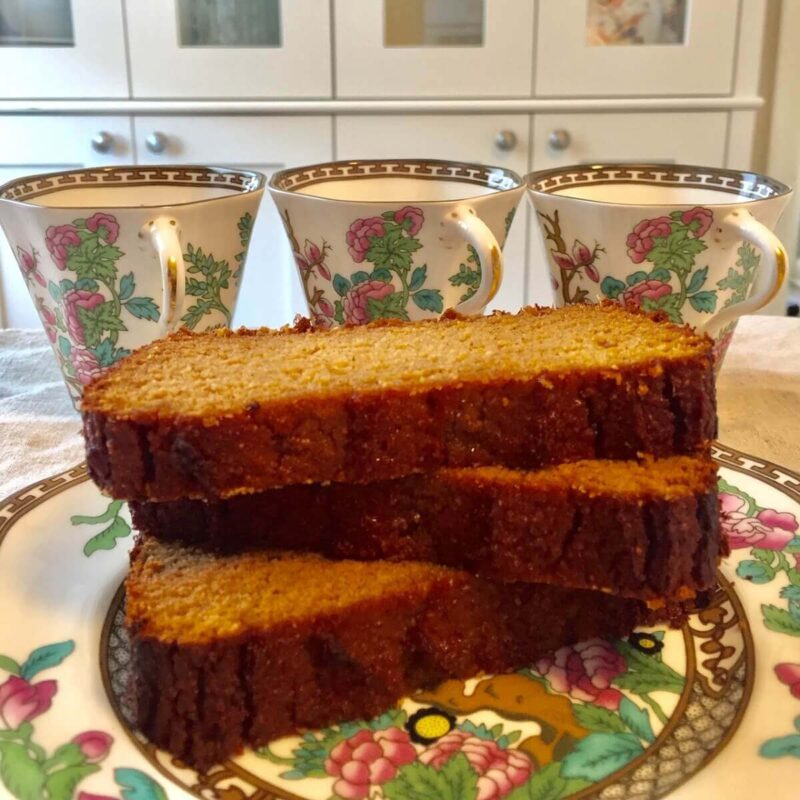 Slices of paleo sweet potato bread stacked on a floral plate next to three cups.