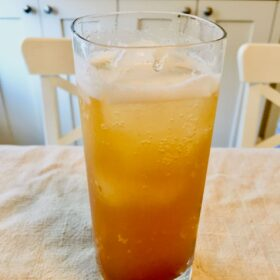 A glass of refined sugar free ginger ale with ice on a linen napkin.
