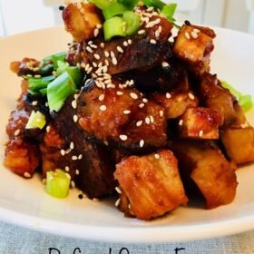 Tofu cubes in a red sauce in a white bowl.
