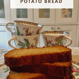 Slices of sweet potato bread stacked in front of three teacups.