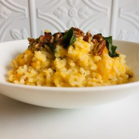 A white bowl filled with vegan butternut squash risotto against a white tile background.