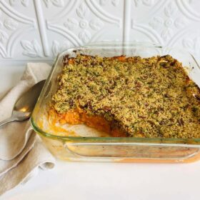 A casserole in a glass baking dish with a scoop missing.