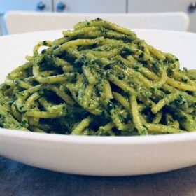 Close up of a white bowl filled with pasta smothered in pesto sauce.