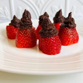 Six chocolate filled strawberries displayed on a white plate.