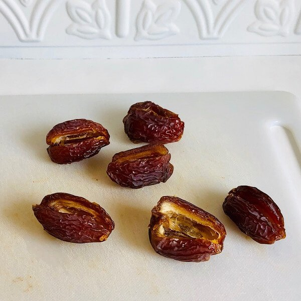 Some pitted dates on a white cutting board.