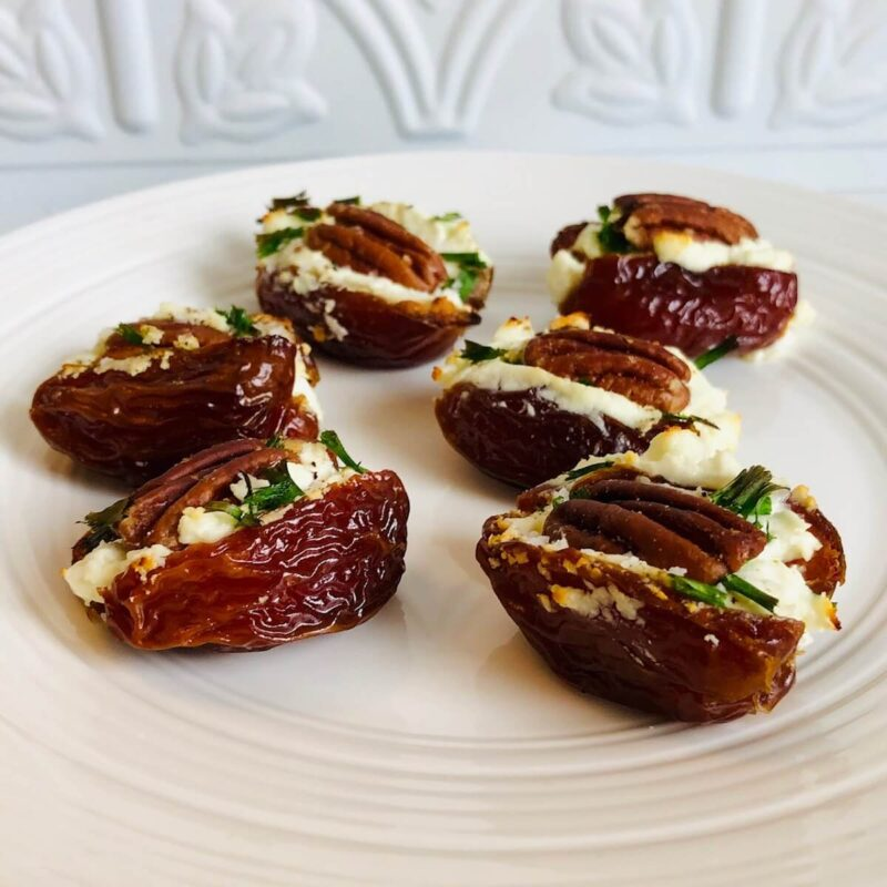 Some goat cheese and pecan stuffed dates arranged on a white platter against a white backsplash.