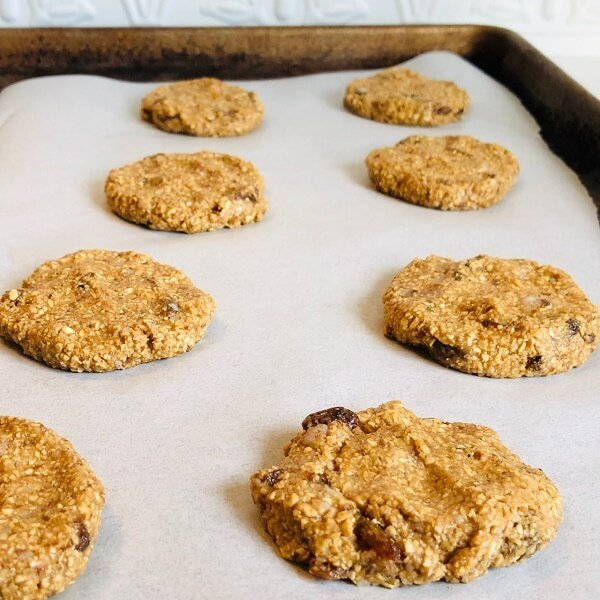 A baking tray of raw oatmeal cookies.