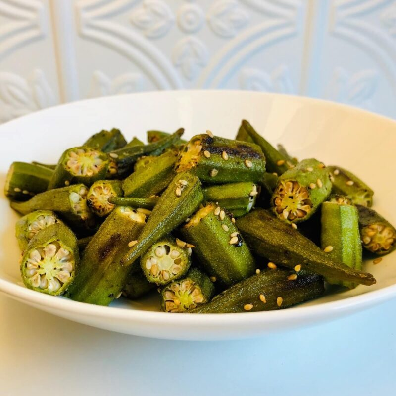 A white bowl filled with oven roasted okra on a counter top.