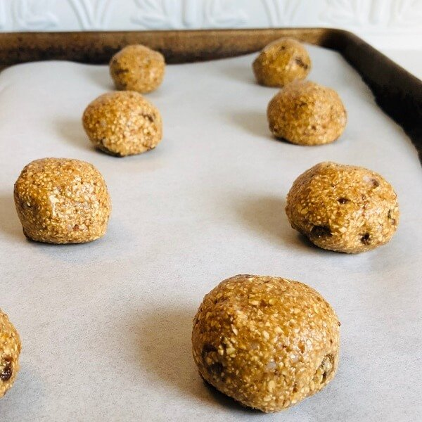 Oatmeal cookies rolled into balls and placed on a baking tray.