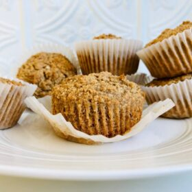 Six vegan applesauce muffins displayed on a white plate.
