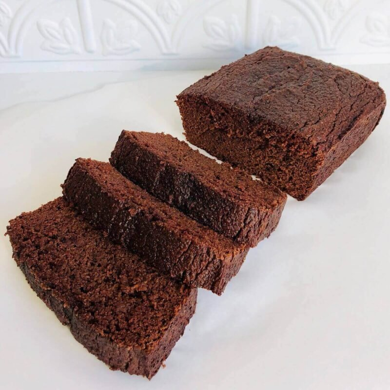 Three slices of paleo chocolate loaf cake next to a larger hunk against a white background.