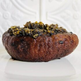 A stuffed mushroom on a white plate against a white tile background.