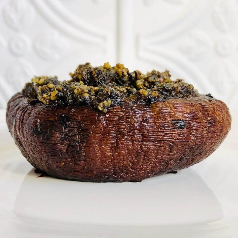 A single vegan stuffed portobello mushroom on a white plate against a white tile background.