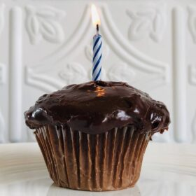 A cupcake topped with tahini frosting with a lit candle in it.