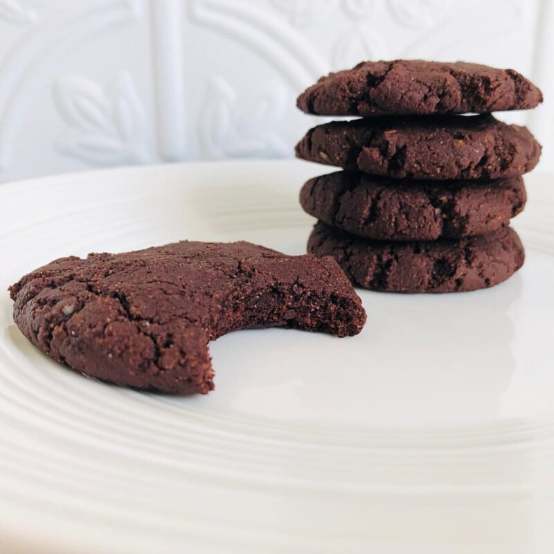 Five vegan brownie cookies on a white plate with a bite missing from one.