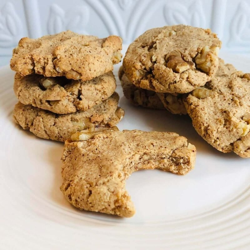 A white plate with a stack of maple walnut cookies with a bite missing from one.
