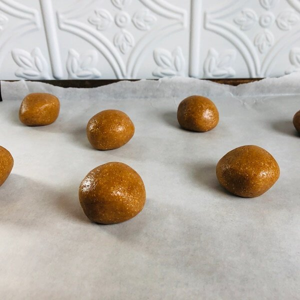 Raw balls of cookie dough on a sheet pan lined with paper.